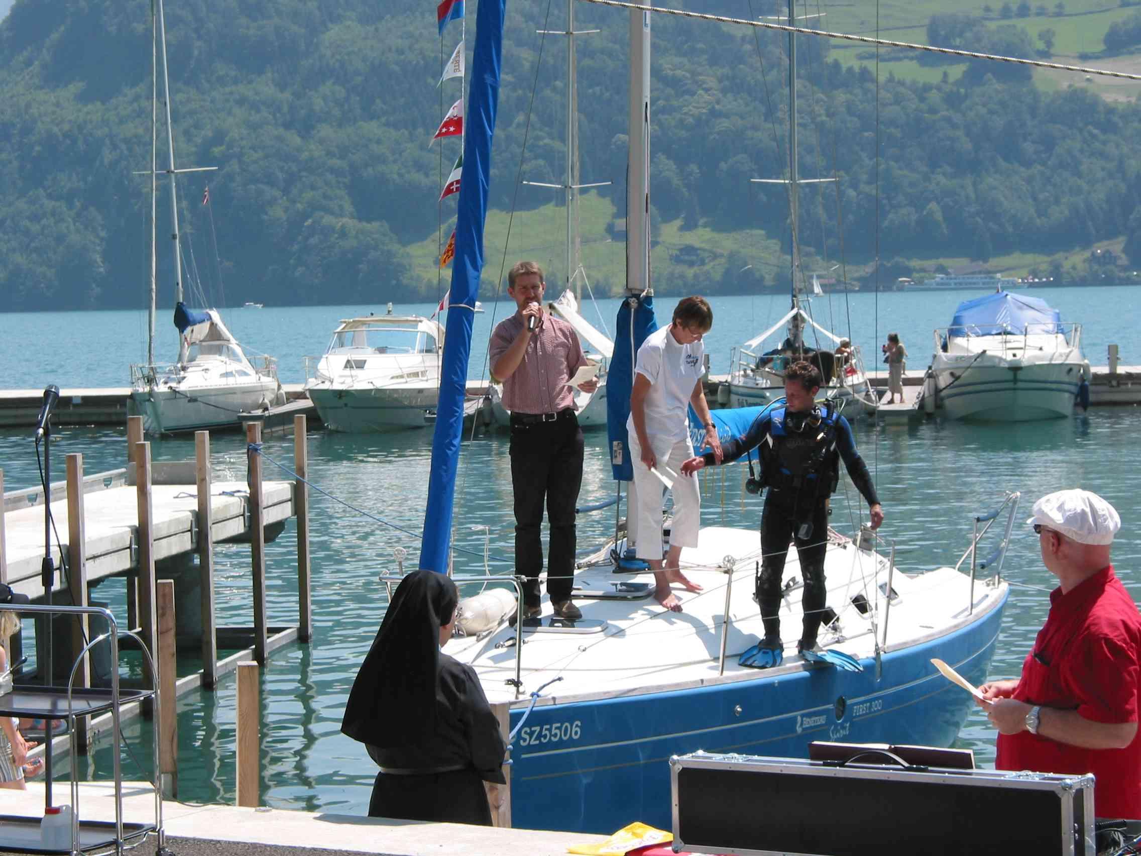 Beginn der ökumenischen Einweihungsfeier. Pfarrer Schüssler erscheint mit seinen Helfern auf einem Segelboot Sr. Servanda und Lukas Albrecht stehen für ihren Einsatz bereit.
